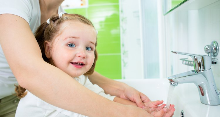 Mother washing kid hands (hand washing) which is very important to prevent infections.